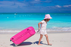 Little adorable girl with big colorful suitcase in hands walking on tropical beach Stock Images
