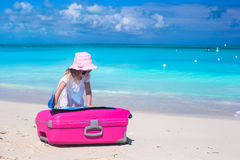Little adorable girl with big colorful suitcase and a map on tropical beach Stock Photos