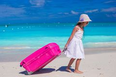 Little adorable girl with big luggage in hands on Royalty Free Stock Photo