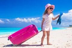 Little adorable girl with big luggage in hands on Royalty Free Stock Photos