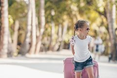 Little adorable girl with big luggage during summer vacation royalty free stock photo