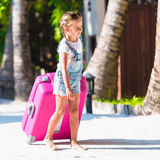 Little adorable girl with big luggage on tropical Stock Images