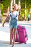 Little adorable girl with big luggage on tropical Royalty Free Stock Image
