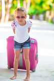 Little adorable girl with big luggage on tropical Royalty Free Stock Photos