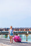 Little adorable girl with big luggage on tropical Royalty Free Stock Photo