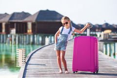 Little adorable girl with big luggage on wooden Stock Image