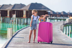 Little adorable girl with big luggage on wooden Stock Photography