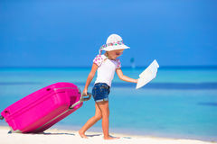 Little adorable girl with big suitcase on tropical Stock Image