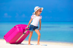 Little adorable girl with big suitcase on tropical Stock Photo