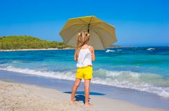 Little adorable girl with big yellow umbrella on Royalty Free Stock Photo