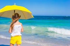 Little adorable girl with big yellow umbrella on Stock Photo