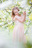 Little adorable girl in blooming cherry tree garden outdoors on Easter eve Stock Photos