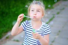 A little adorable girl blowing soap bubbles. At park Stock Photos