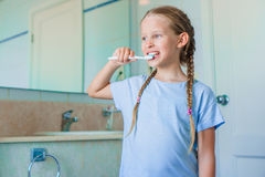 Little adorable girl brushes teeth in the bathroom. Perfect snow-white smile of little girl Stock Images