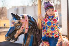 Little adorable girl on carousel at sunny day Royalty Free Stock Images