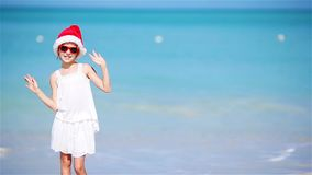 Little adorable girl in Christmas hat on white beach during Xmas vacation. Happy smiling kid looking at camera stock footage
