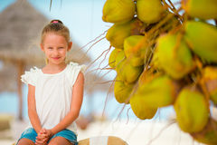 Little adorable girl with coconut on white tropical beach Royalty Free Stock Photo
