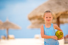 Little adorable girl with coconut on white tropical beach Royalty Free Stock Photos