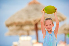Little adorable girl with coconut on white tropical beach Royalty Free Stock Photography