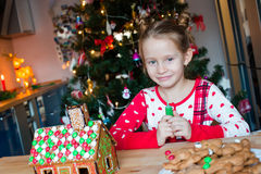 Little adorable girl cooking gingerbread house for Royalty Free Stock Images