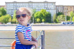 Little adorable girl on the deck of a ship sailing in big city Royalty Free Stock Photography