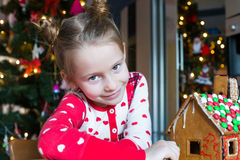 Little adorable girl decorating gingerbread house Royalty Free Stock Images