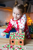 Little adorable girl decorating gingerbread house Royalty Free Stock Image