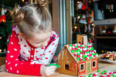 Little adorable girl decorating gingerbread house Stock Photo