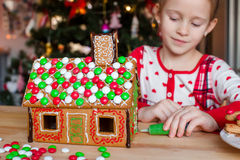 Little adorable girl decorating gingerbread house Stock Photography