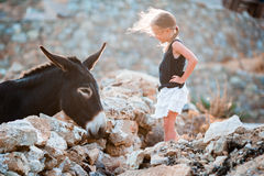 Little adorable girl with donkey on Mykonos Royalty Free Stock Image