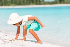 Adorable little girl drawing picture on white beach royalty free stock photos