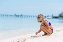 Adorable little girl drawing picture on white beach stock photos
