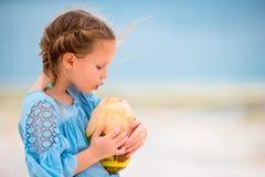 Little adorable girl drinking coconut milk on the beach Stock Photo