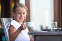 Little adorable girl drinking tea on breakfast in Stock Photography
