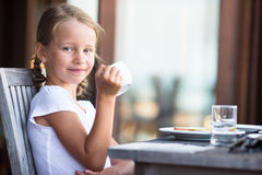 Little adorable girl drinking tea on breakfast in Stock Images