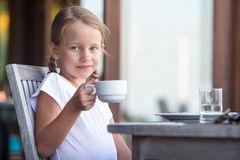 Little adorable girl drinking tea on breakfast in Royalty Free Stock Images