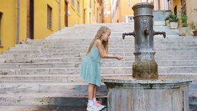 Little adorable girl drinking water from the tap outside at hot summer day in Rome, Italy stock footage