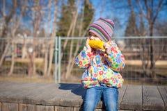 Little adorable girl eating corn outdoors Stock Photos