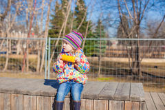 Little adorable girl eating corn in the park on a warm spring day Royalty Free Stock Image