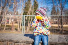 Little adorable girl eating corn in the park on a warm spring day Royalty Free Stock Images
