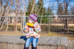Little adorable girl eating corn in the park on Royalty Free Stock Photos