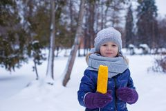 Little adorable girl eating corn in winter park Royalty Free Stock Images