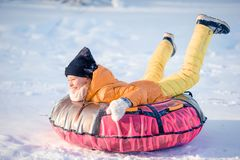 Adorable little happy girl sledding in winter snowy day. royalty free stock photos