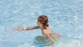 Little girl playing in transparent water royalty free stock image
