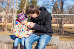 Little adorable girl and father eating corn in the park on a warm spring day Stock Image