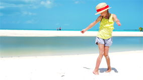 Little adorable girl in hat on white tropical beach. SLOW MOTION. Cute little girl in hat at beach during caribbean vacation stock footage