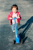 Little adorable girl having fun riding on scooter stock photo