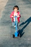 Little adorable girl having fun riding on scooter royalty free stock photo