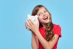 Happy girl shaking piggy box Royalty Free Stock Photography