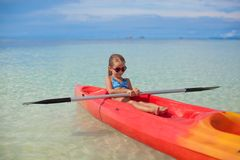 Little adorable girl kayaking in clear blue sea Stock Images